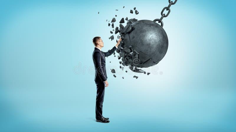 Un hombre de negocios en el fondo azul que toca una bola arruinadora cuando se estrella bajo su mano fotografía de archivo