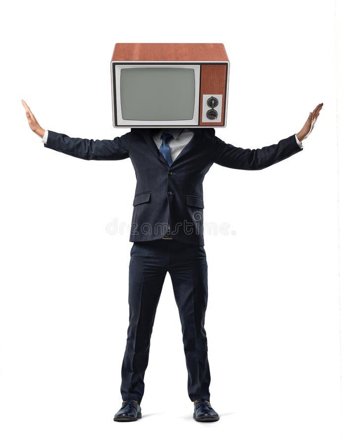 Un hombre de negocios en fondo aislado hace su cabeza substituir por una TV retra y se sostiene los brazos aumentados en lados imagenes de archivo
