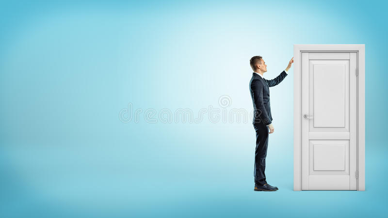 Un hombre de negocios en fondo azul toca un doorframe blanco con un interior a puerta cerrada imagen de archivo libre de regalías