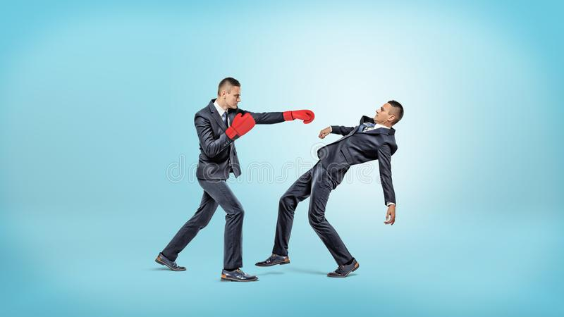 Un hombre de negocios en guantes de boxeo no puede perforar a otro hombre que maneje evitar el retroceso imagen de archivo libre de regalías