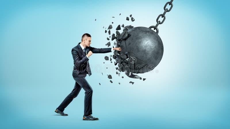 Un hombre de negocios en la altura completa que perfora y que rompe una bola arruinadora enorme en fondo azul imagen de archivo libre de regalías