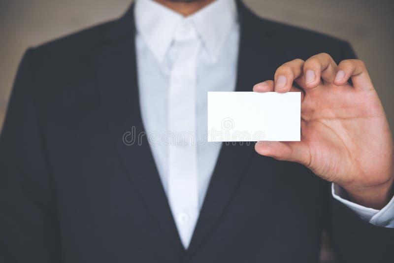 Un hombre de negocios en la camisa blanca y el traje gris que muestran la tarjeta de visita vacía fotografía de archivo