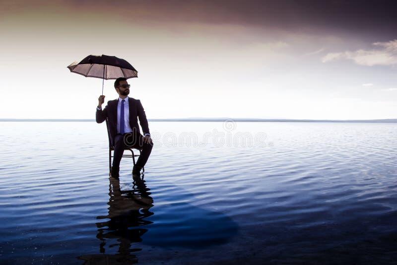 Un hombre de negocios en un traje con un paraguas fotos de archivo libres de regalías