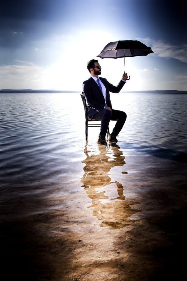 Un hombre de negocios en un traje con un paraguas fotografía de archivo libre de regalías