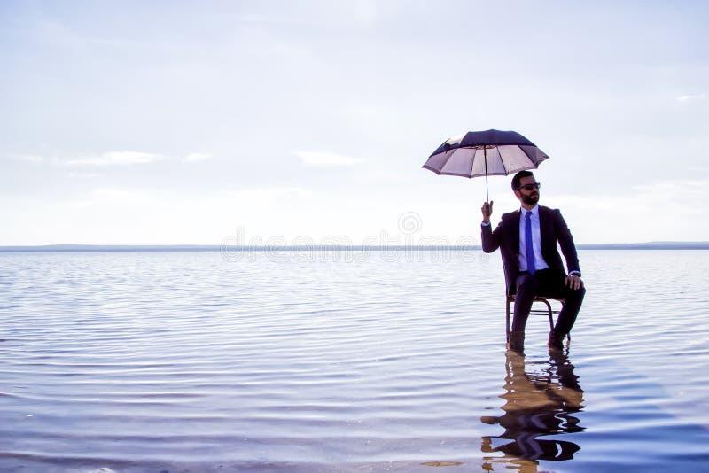Un hombre de negocios en un traje con un paraguas imagenes de archivo