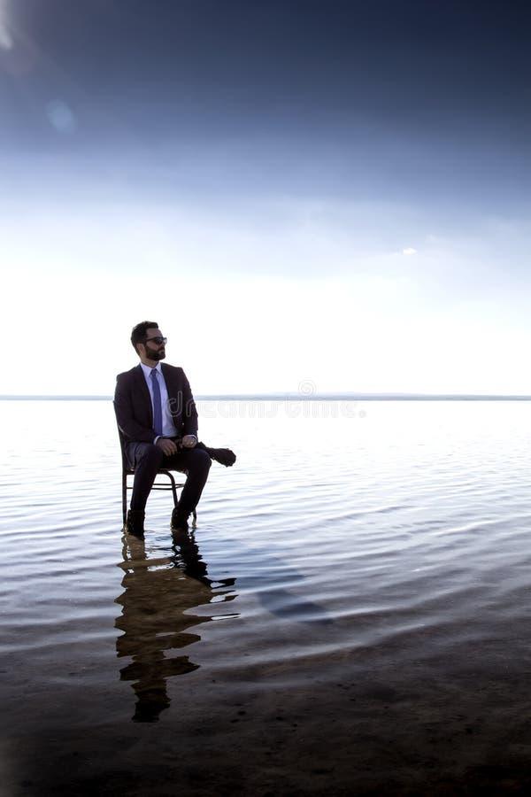 Un hombre de negocios en un traje en el agua imagen de archivo