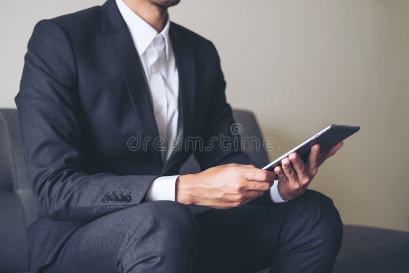 Un hombre de negocios en un traje gris que se sienta en la tenencia del sofá, usando en la PC de la tableta para el trabajo en of imagen de archivo libre de regalías