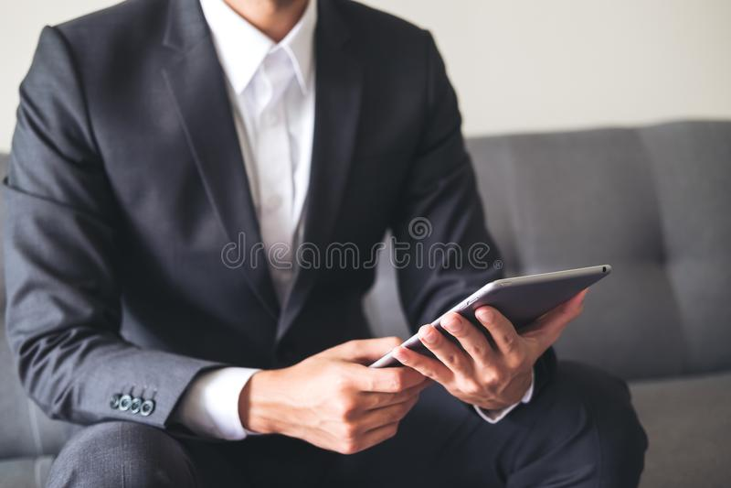 Un hombre de negocios en un traje gris que se sienta en la tenencia del sofá, usando y mirando la PC de la tableta para el trabaj imagenes de archivo