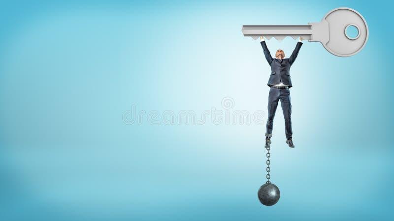 Un hombre de negocios encadenado a una bola del hierro vuela ascendente mientras que lleva a cabo una llave enorme del metal imagenes de archivo