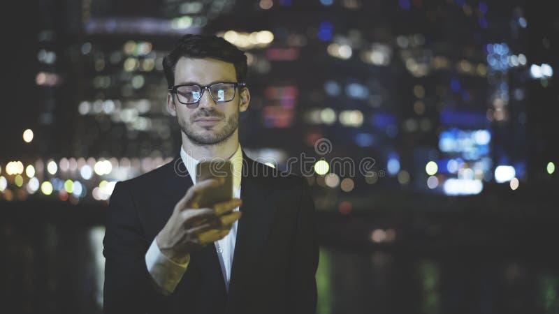 Un hombre de negocios está mandando un SMS a un mensaje en el teléfono en la noche foto de archivo libre de regalías