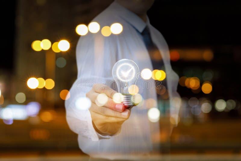 Un hombre de negocios está mostrando una bombilla brillante con símbolo de la perspectiva dentro en el fondo ocupado de la ciudad fotos de archivo libres de regalías