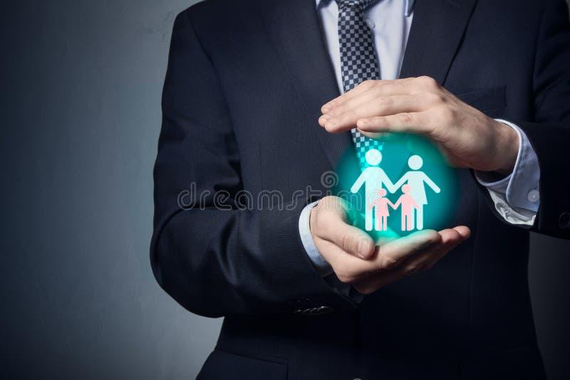 Un hombre de negocios está sosteniendo un pictograma de la familia en su mano Protección de la familia y del matrimonio imágenes de archivo libres de regalías