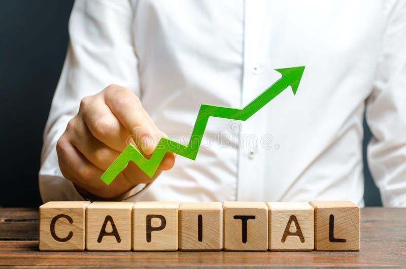 Un hombre de negocios est? sosteniendo una flecha ascendente verde sobre el capital de la palabra Aumento de la atracci?n de las  foto de archivo libre de regalías