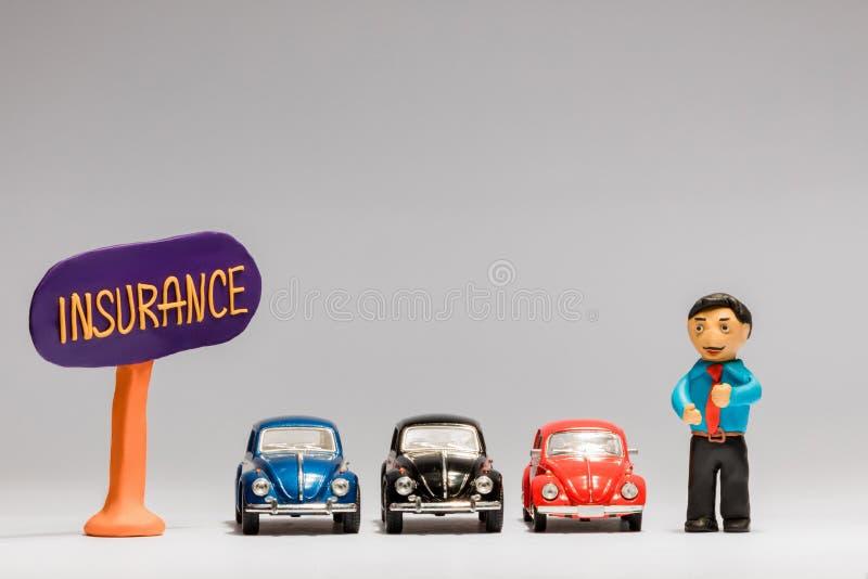 Un hombre de negocios hecho del plasticine al lado de tres coches y de una muestra del seguro, en el fondo blanco foto de archivo libre de regalías