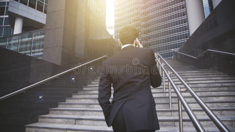 Un hombre de negocios hermoso que camina encima de las escaleras y que tiene conversación telefónica imagen de archivo