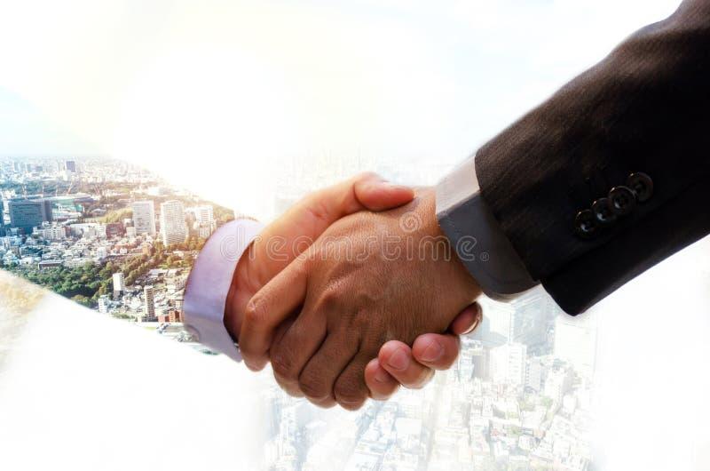 Un hombre de negocios inversor da la mano con su socio para lograr un acuerdo de reunión exitoso durante el amanecer y el paisaje foto de archivo libre de regalías