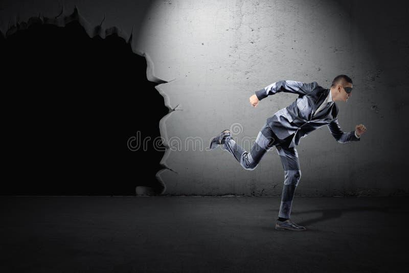 Un hombre de negocios joven apto en un traje rayado y una máscara negra que corren lejos de un calabozo en una pared imagen de archivo