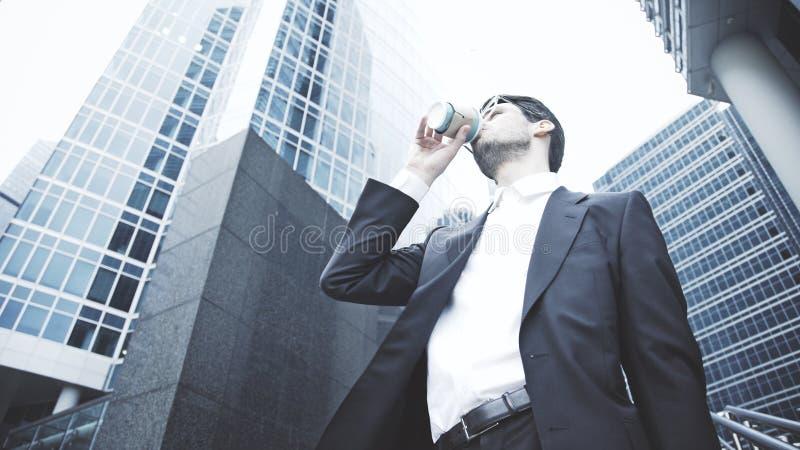 Un hombre de negocios joven bebe el café en la calle imagenes de archivo
