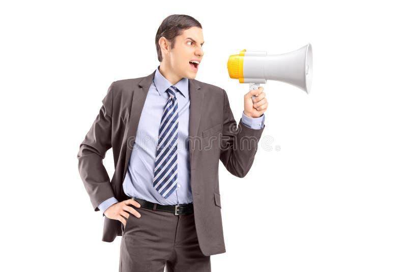 Un hombre de negocios joven enojado que anuncia vía el megáfono fotos de archivo libres de regalías