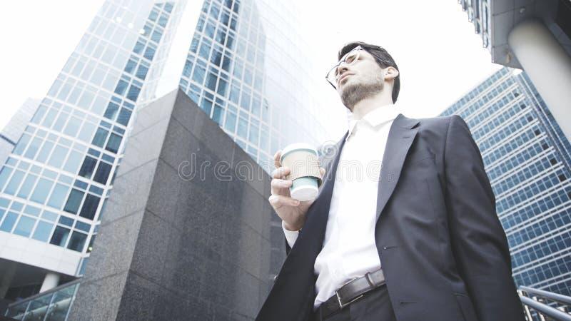 Un hombre de negocios joven está sosteniendo una taza de café en la calle imagenes de archivo