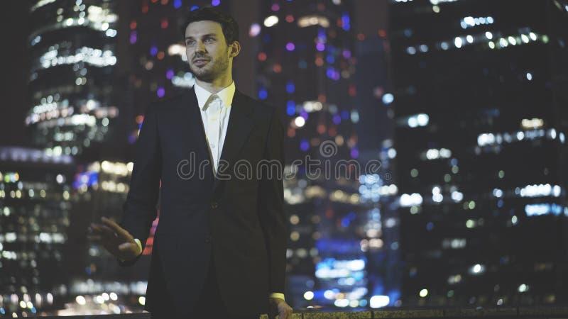 Un hombre de negocios joven que hablaba se vistió en un traje negro en la noche imagen de archivo