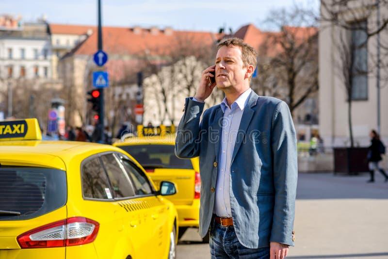 Un hombre de negocios de la Edad Media en la estación del taxi imagen de archivo