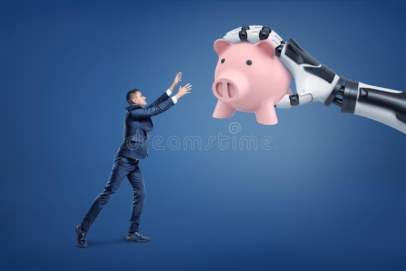 Un hombre de negocios minúsculo pierde una hucha rosada grande a una mano robótica gigante foto de archivo