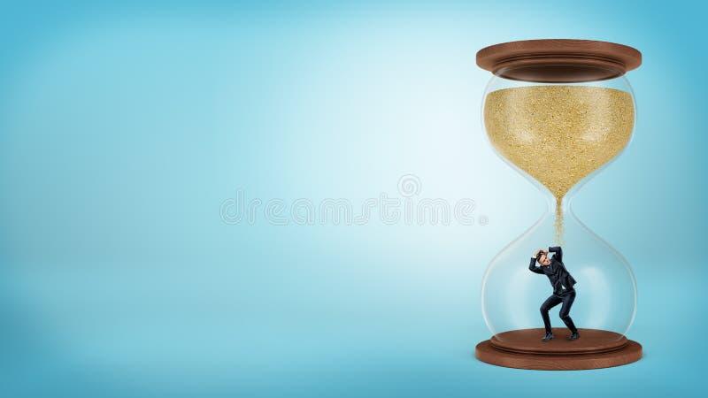 Un hombre de negocios minúsculo se coloca dentro de un reloj de arena cuando la arena comienza solamente a caer sobre él imagen de archivo