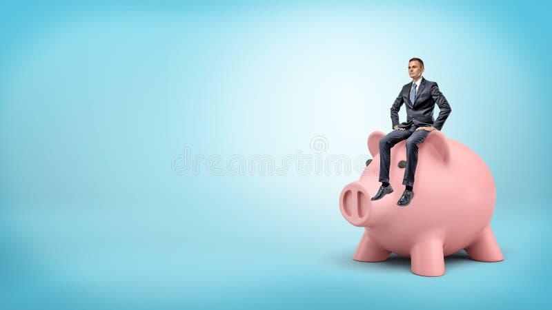 Un hombre de negocios minúsculo se sienta tranquilamente en una cabeza gigante del ` s de la hucha en fondo azul imagen de archivo