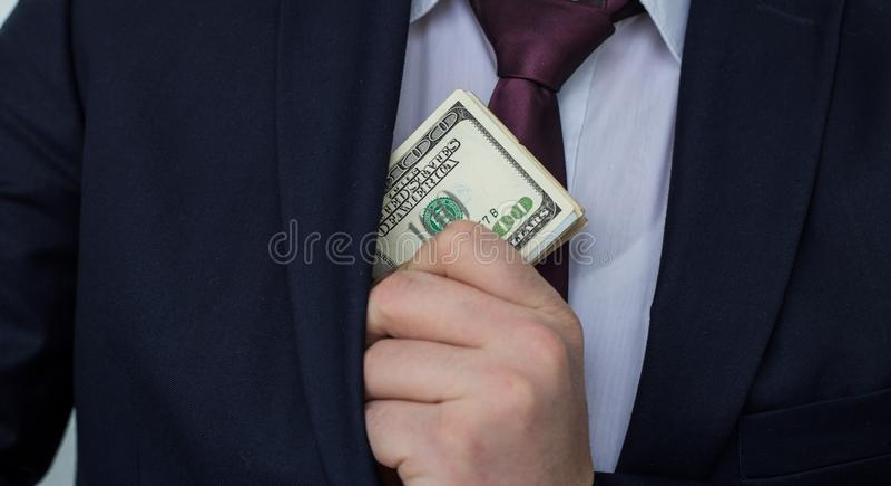 Un hombre de negocios muestra una suma de efectivo, la pone en su bolsillo del traje fotos de archivo libres de regalías