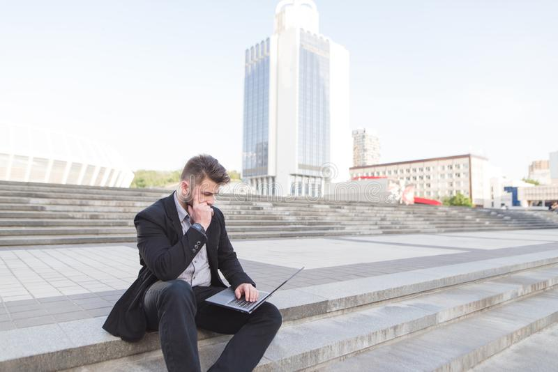 Un hombre de negocios pensativo que se sienta en una escalera con un ordenador portátil en sus rodillas contra un contexto del pa fotografía de archivo