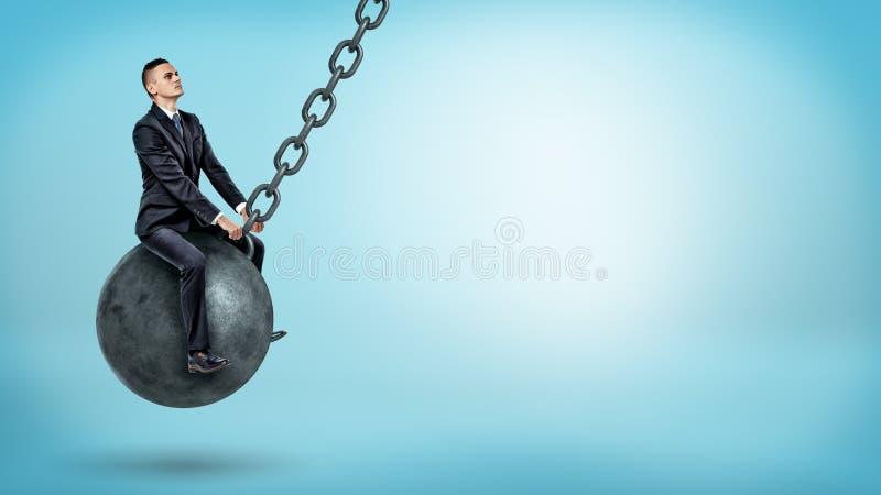 Un hombre de negocios que balancea en una bola arruinadora grande y que mira para arriba en fondo azul fotos de archivo libres de regalías