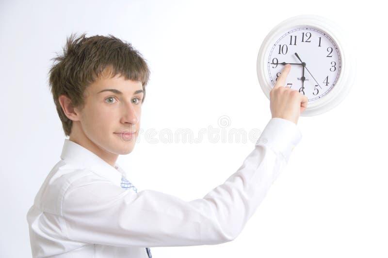Un hombre de negocios que cambia el tiempo en los clo de la oficina foto de archivo