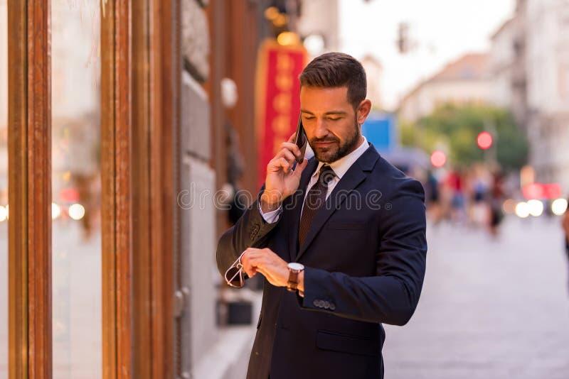 Un hombre de negocios que comprueba un escaparate y que habla en su teléfono imagen de archivo libre de regalías