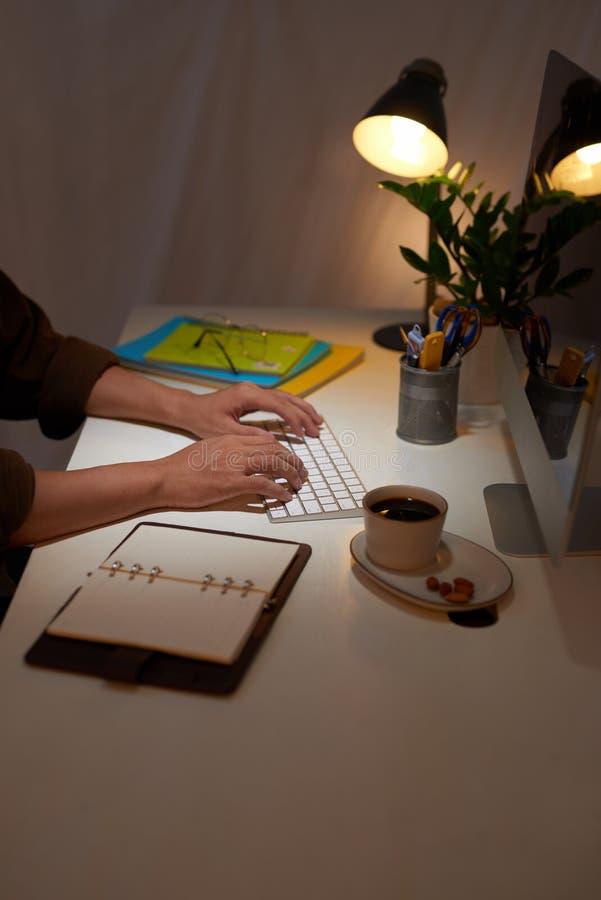 Un hombre de negocios que escribe notas en un coj?n de escritura mientras que se sienta en su escritorio de trabajo con caf? foto de archivo