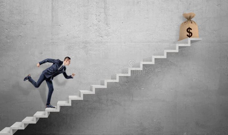 Un hombre de negocios que funciona con para arriba una escalera concreta con un bolso atado de la arpillera con una muestra de dó imagen de archivo libre de regalías