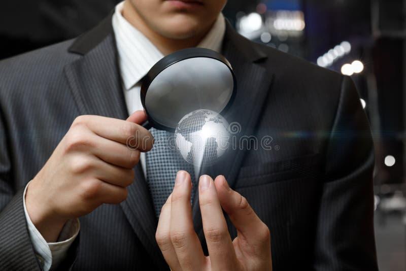 Un hombre de negocios que mira un globo a través de la lupa stock de ilustración