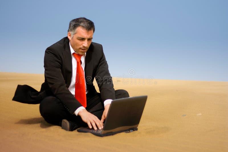 Un hombre de negocios que se relaja y se sienta en la arena fotografía de archivo