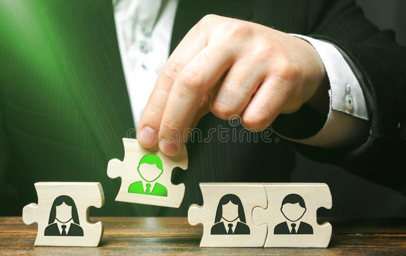 Un hombre de negocios recoge los rompecabezas que simbolizan a un equipo de empleados El concepto de crear a un equipo del negoci foto de archivo