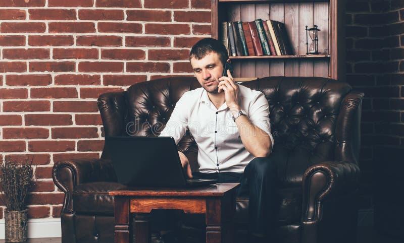 Un hombre de negocios se sienta en el sofá y las llamadas del teléfono Un interior elegante del cuarto rodea al hombre rico fotografía de archivo libre de regalías