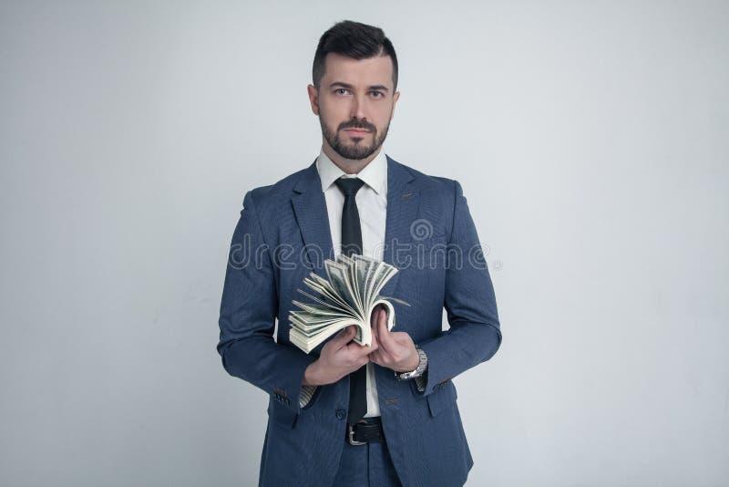 Un hombre de negocios serio cuenta el dinero vestido en un traje y miradas de la moda en la cámara Ganó la lotería en un blanco imagen de archivo