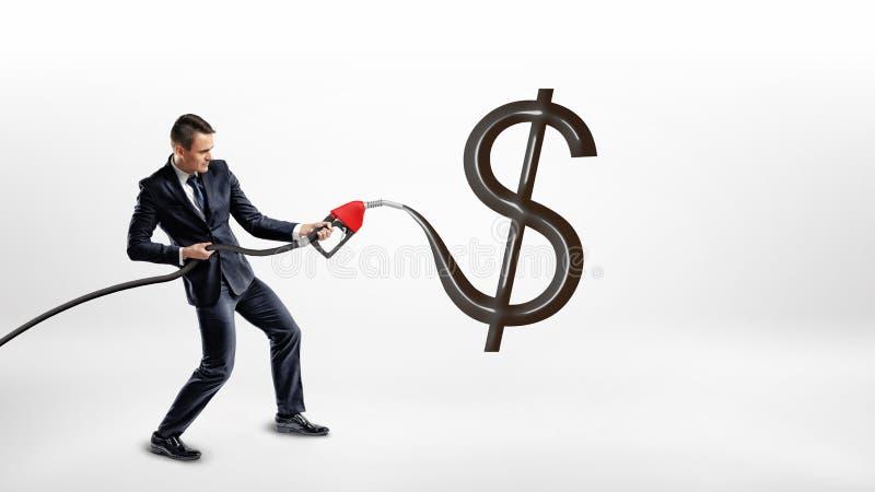 Un hombre de negocios sostiene una boca de la bomba de gas y hace una muestra brillante negra enorme de USD en un fondo blanco fotos de archivo libres de regalías
