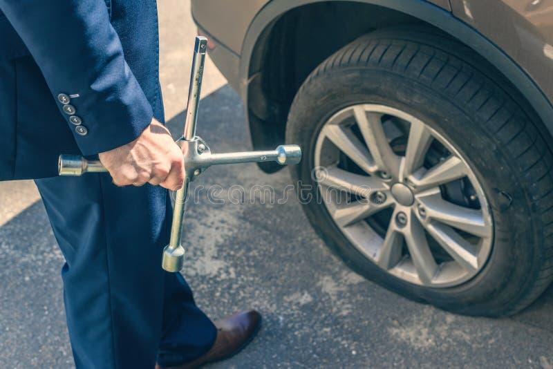Un hombre de negocios de traje azul con llave cruzada apriete los tornillos y la rueda de la rueda perforada Agujero en el neumát fotos de archivo