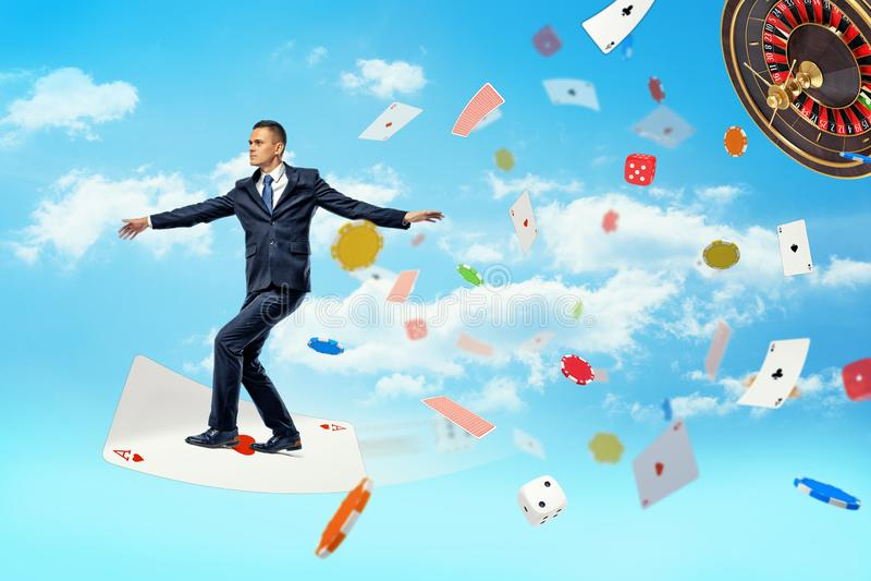 Un hombre de negocios vuela la situación en un naipe grande y rodeada volando tarjetas, microprocesadores y dados foto de archivo libre de regalías