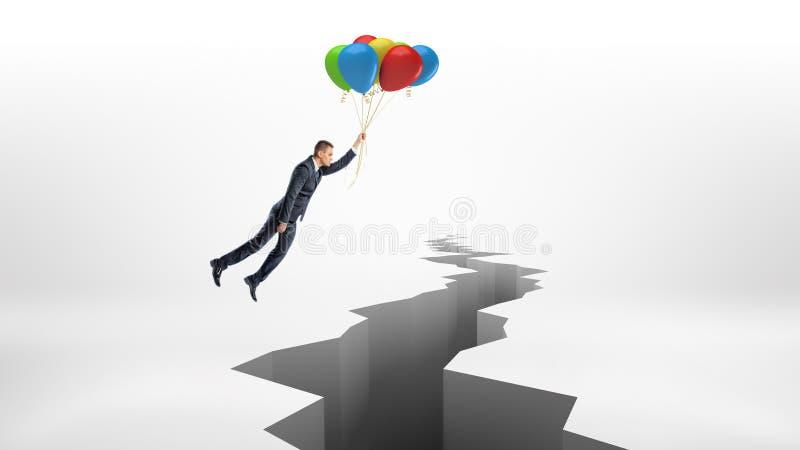 Un hombre de negocios vuela sobre una grieta enorme en la superficie blanca mientras que sostiene un manojo de globos coloridos fotografía de archivo