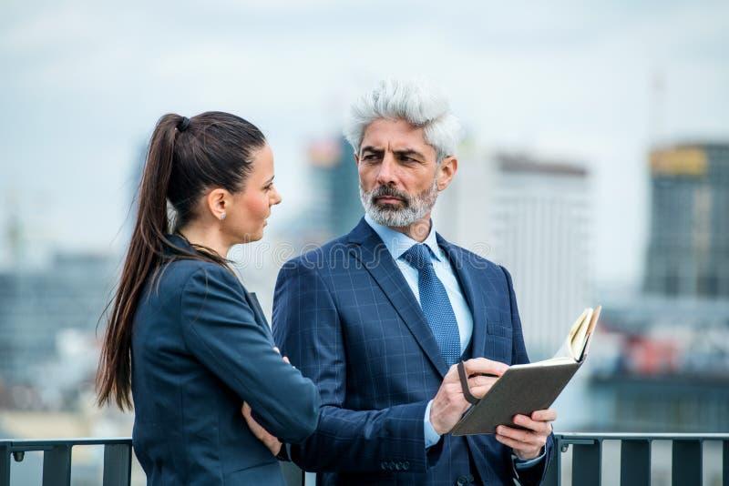 Un hombre de negocios y una mujer de negocios con un diario en la terraza, trabajando imagen de archivo libre de regalías