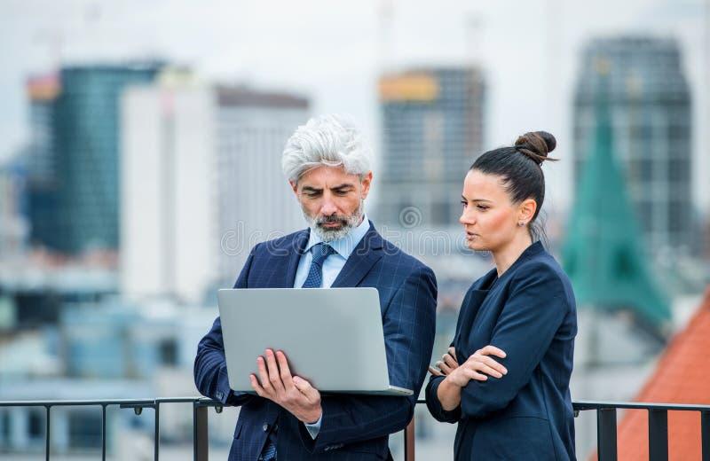 Un hombre de negocios y una mujer de negocios con un ordenador portátil en la terraza, trabajando fotos de archivo libres de regalías