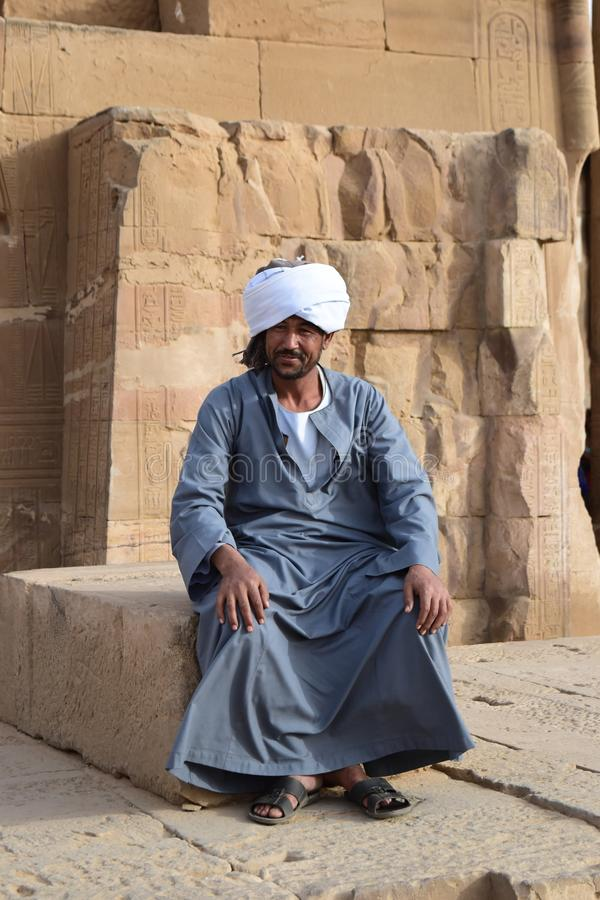 Un hombre de Nubian que se sienta en un templo en Egipto, Asuán Luxor imagenes de archivo