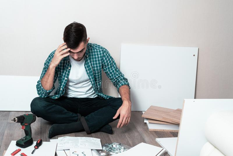 Un hombre de pensamiento que se sienta en los muebles de junta del piso según instrucciones imagenes de archivo