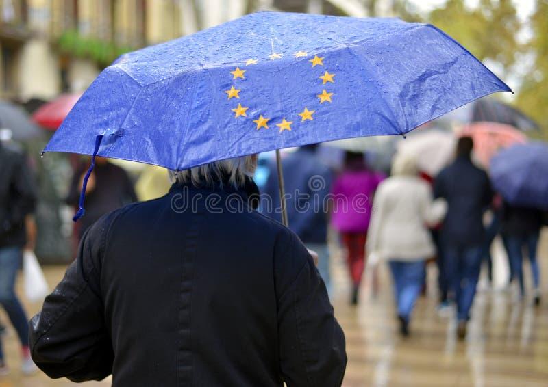 Un hombre debajo de un paraguas con un símbolo de la unión europea imagen de archivo libre de regalías